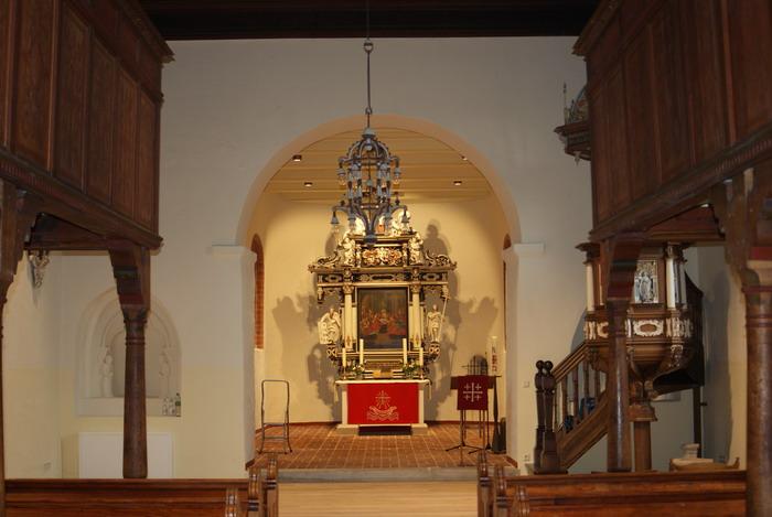 Blick durch das Kirchenschiff zum bestens ausgeleuchteten Altar.