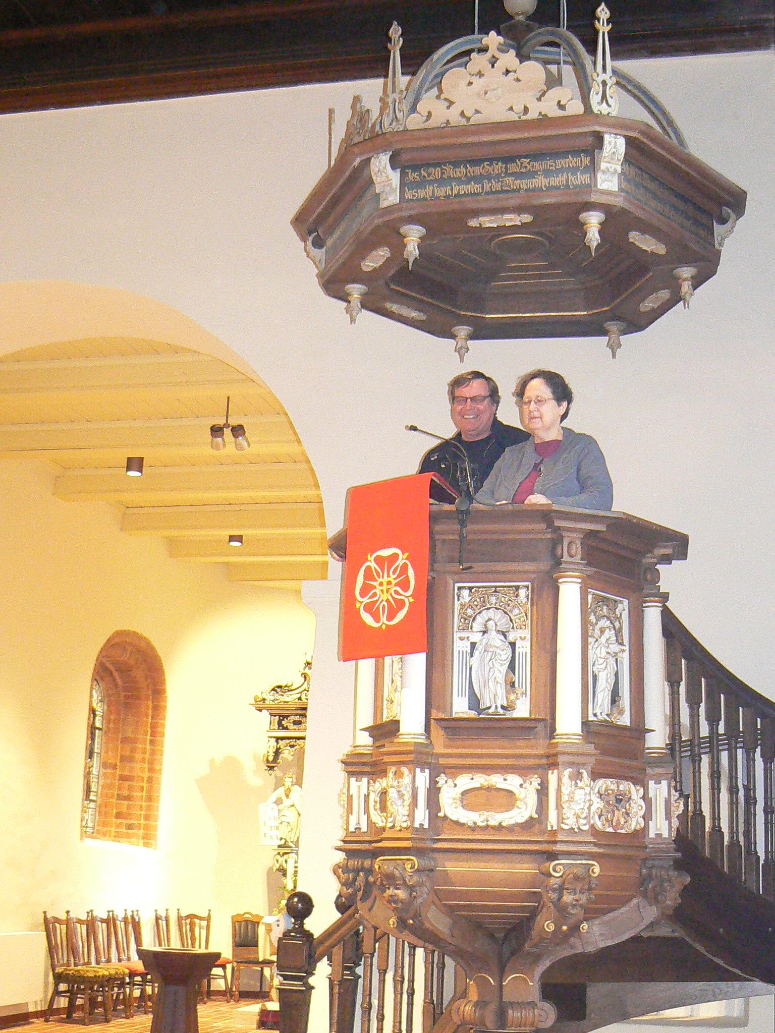 Pastorin Susanne Franz und Pastor Burkhard Ziemens auf der Kanzel, die versetzt wurde und sich jetzt auf der rechten Seite vor dem Altarraum befindet und nicht mehr dem Blick auf den Altar verdeckt.